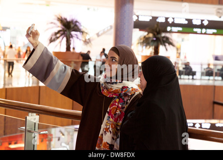Two muslim arab women taking a selfie on a mobile phone, the Dubai Mall, UAE, United Arab Emirates Middle East - Stock Photo