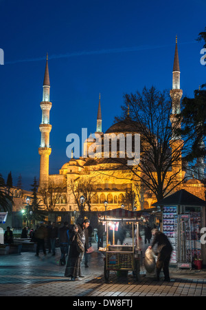 Early evening strollers in front of a floodlit Sultan Ahmet or Blue Mosque, Sultanahmet, Istanbul, Turkey - Stock Photo