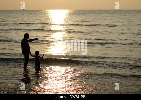 Man and child on a beach at sunset, Koh Kood, Thailand. - Stock Photo