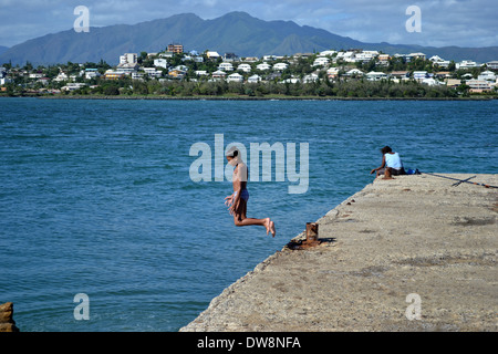 Kids playing at the pier in Port Despointes, St. Mary's Bay, Noumea, New Caledonia, South Pacific - Stock Photo