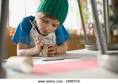 Boy making clay figurine in art class - Stock Photo