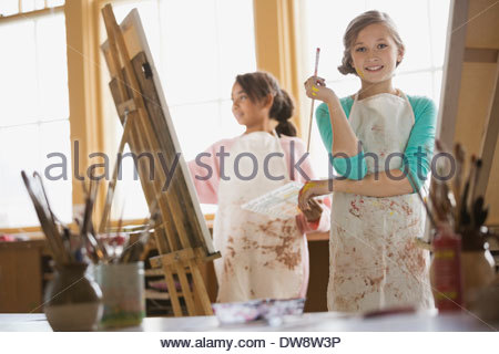 Portrait of confident girl painting in art class - Stock Photo
