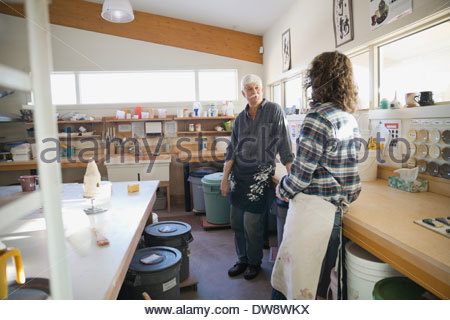 Pottery members talking in studio - Stock Photo