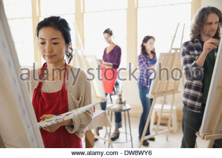 Female student painting in art class - Stock Photo