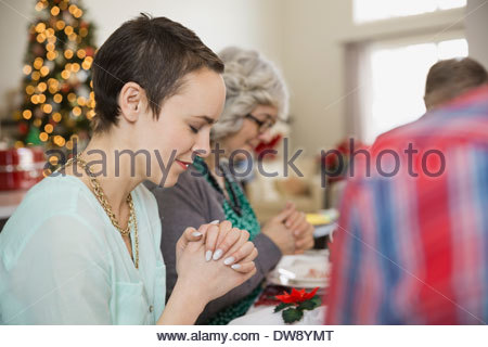 Multi-generation family saying grace before Christmas dinner - Stock Photo