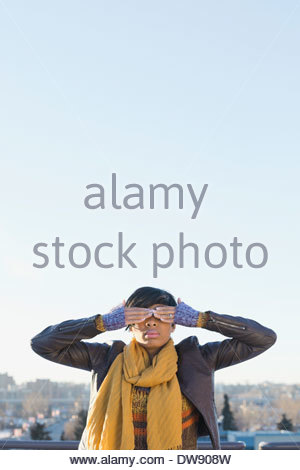 Woman covering eyes with two hands outdoors - Stock Photo