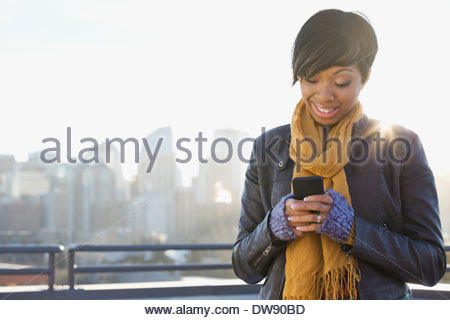 Smiling woman text messaging on patio - Stock Photo
