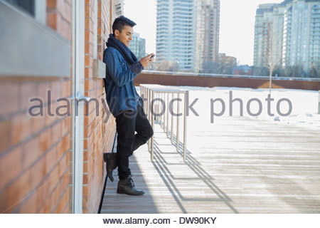 Man text messaging using smart phone outdoors - Stock Photo