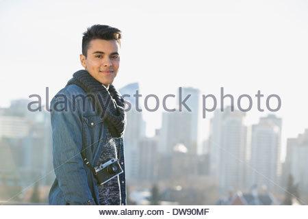 Portrait of confident man standing against cityscape - Stock Photo