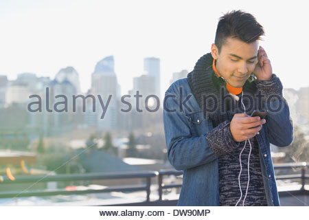 Man listening to music on smart phone outdoors - Stock Photo