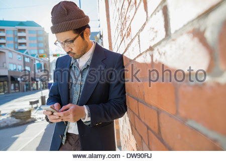 Man text messaging on smart phone against brick wall - Stock Photo