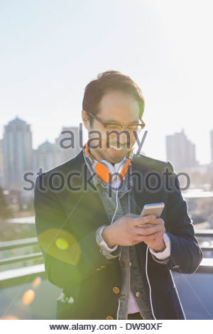 Smiling man listening to music on smart phone - Stock Photo