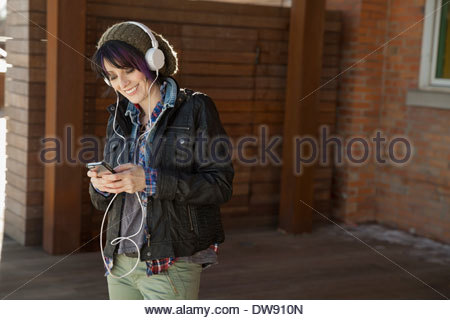 Smiling woman listening to music on headphones outdoors - Stock Photo