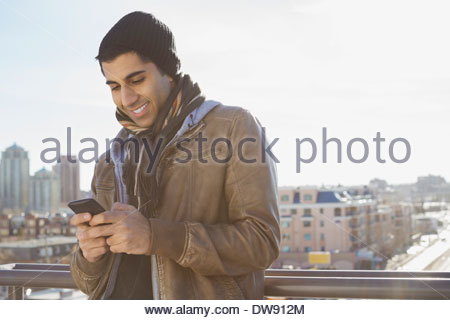 Smiling man text messaging outdoors - Stock Photo