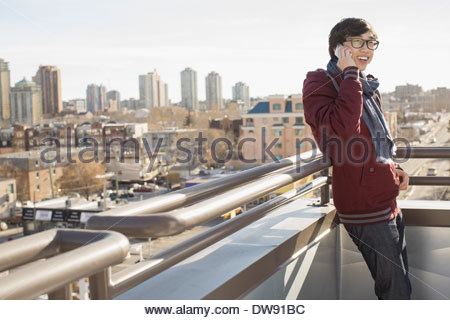 Smiling young man answering smart phone on patio - Stock Photo