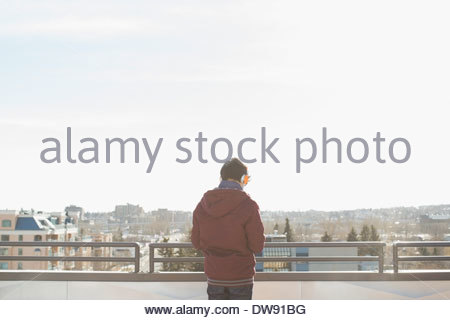 Rear view of young man looking out at city view - Stock Photo