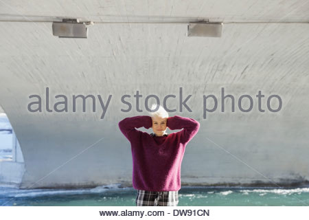 Portrait of woman with hands covering ears standing under city bridge - Stock Photo