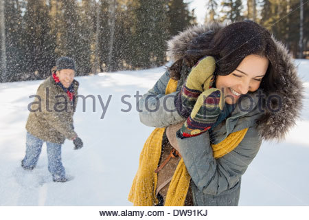 Couple having snowball fight - Stock Photo