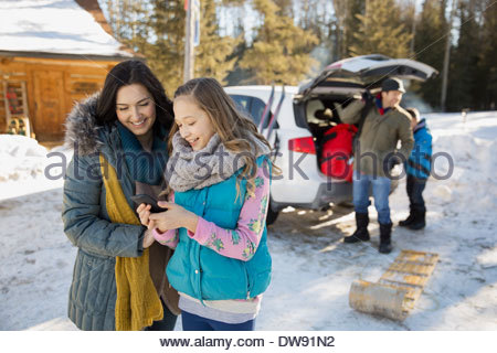 Mother and daughter using smart phone outdoors - Stock Photo