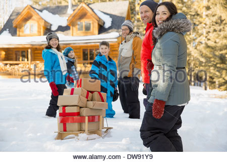 Family walking to cabin with stack of gifts - Stock Photo