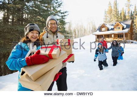 Portrait of senior couple holding Christmas presents outdoors - Stock Photo