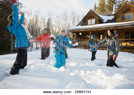 Playful family having snowball fight - Stock Photo