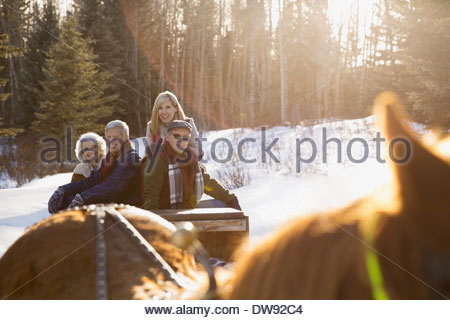 Smiling friends riding on horse-drawn sleigh - Stock Photo