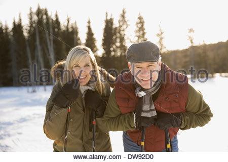 Portrait of smiling couple holding ski poles outdoors - Stock Photo