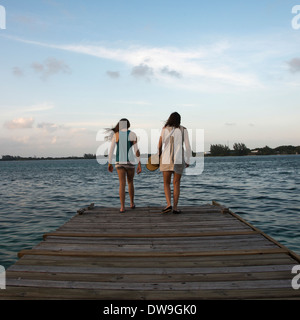 Woman with her daughter standing on a pier and looking at sea Utila Island Bay Islands Honduras - Stock Photo