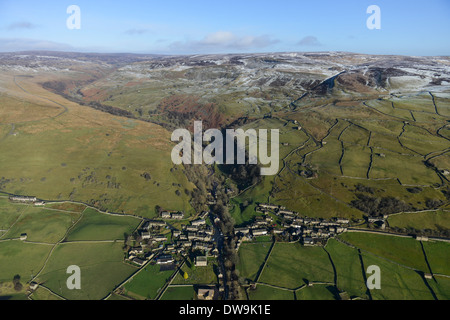 Aerial Photograph showing Gunnerside in the Yorkshire Dales in Winter with Snowy Peaks and a Valley in the Background - Stock Photo