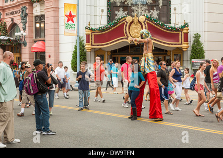 Egyptian stiltwalker poses with guests on the street at Universal Studios theme park in Orlando, Florida - Stock Photo