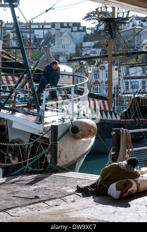 sailors preparing to set sail in Brixham Devon,watched by homeless lady - Stock Photo