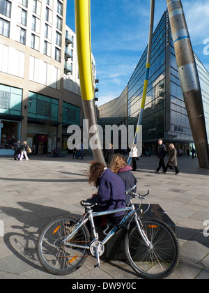 Women and bicycle outside John Lews store and Cardiff Central LIbrary in city centre Cardiff Wales UK KATHY DEWITT - Stock Photo