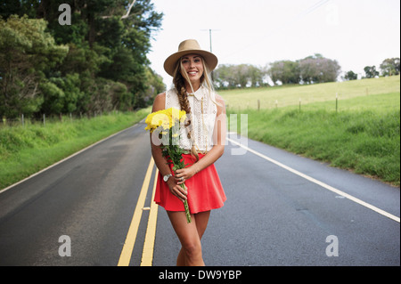 Young woman with flowers on road - Stock Photo