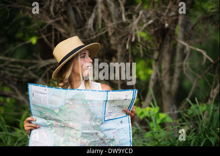 Young woman with map in forest - Stock Photo