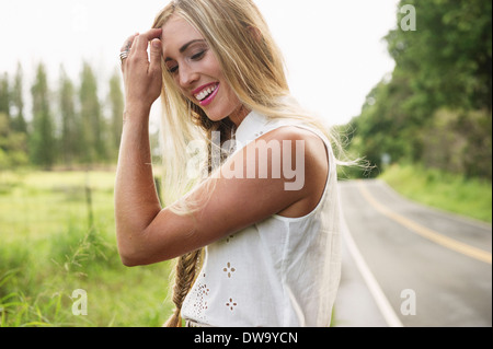 Young woman standing on roadside - Stock Photo