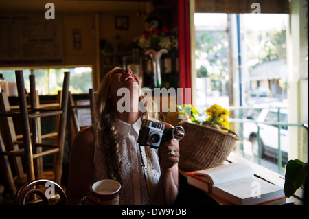 Young woman with camera in cafe - Stock Photo