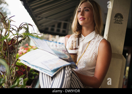 Young woman with map daydreaming - Stock Photo