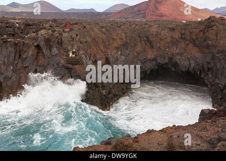 Tourists on a viewing balcony above a large wave crashing against cliffs at Costa Los Hervideros Lanzarote Canary - Stock Photo