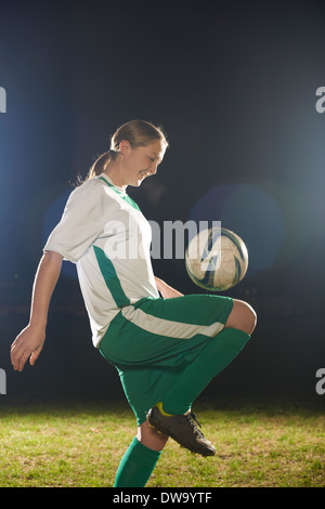 Female soccer player bouncing ball on knee - Stock Photo