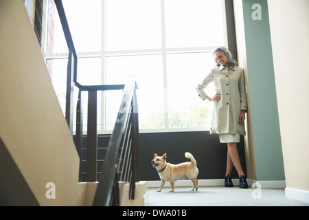 Mature woman and pet dog on stairwell - Stock Photo