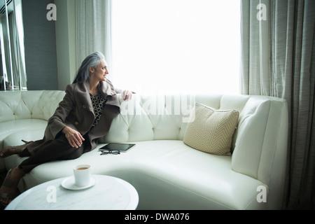 Portrait of mature woman reclining on white luxury sofa - Stock Photo