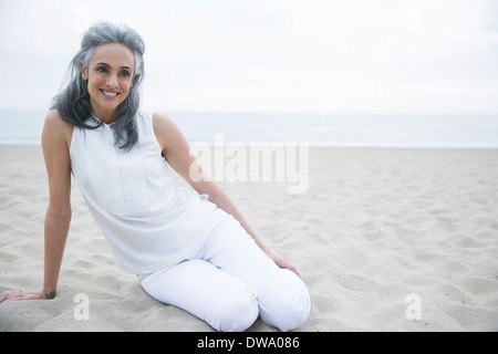 Mature woman relaxing on beach, Los Angeles, California, USA - Stock Photo