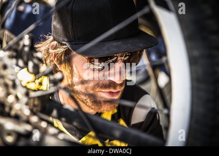 Close up of young male mountain biker checking bike wheel - Stock Photo