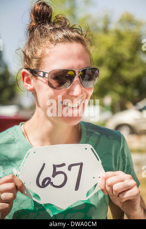 Young female mountain biker holding up race number - Stock Photo