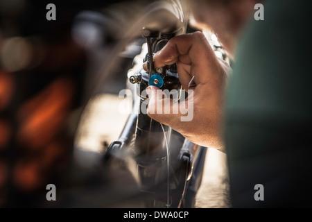 Close up of young male mountain biker repairing bike - Stock Photo