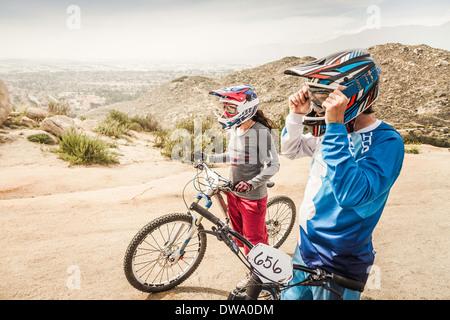 Male and female mountain bikers at race start line, Fontana, California, USA - Stock Photo