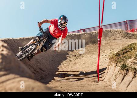 Young male mountainbiker racing in Sea Otter Classic Mountainbike Festival on Laguna Seca Raceway near Monterey - Stock Photo