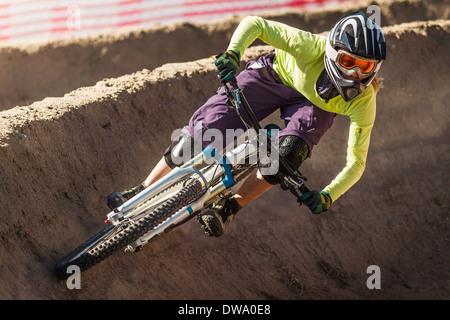 Young female mountainbiker racing in Sea Otter Classic Mountainbike Festival on Laguna Seca Raceway near Monterey - Stock Photo