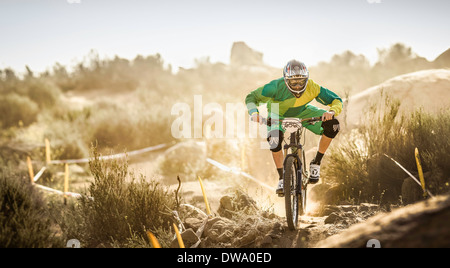 Male mountain biker racing on dusty dirt track, Fontana, California, USA - Stock Photo